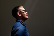Side view of smiling handsome young red-bearded man in eyeglasses looking at light in dark room, ambitions concept