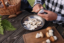 Man Slicing Mushrooms At Wooden Table Outdoors, Closeup