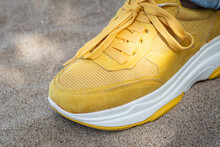Yellow Sneaker On The Sand. Shoes For Sports And Travel.