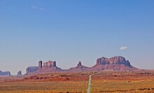 Long Road Leading To Outcropping Mountains In Monument Valley, Utah