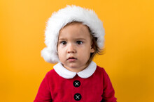 Serious Portraite Cute Happy Cheerful Chubby Baby Girl In Santa Hat Looking On Camera At Yellow Background. Child Play Christmas Scene Celebrating Birthday. Kid Have Fun Spend New Year Time Copy Space