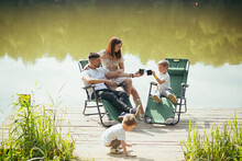Happy Young Family With Toddler Children Resting Sitting On Folding Camping Chairs Over Lake On A Wooden Pier Outdoors. Spend Leisure Time Together In Camp Pontoon With Kids In Nature. Vacation Forest