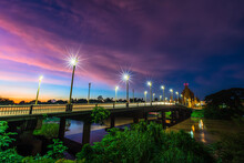 The Color Of Night Traffic Light On The Road On The Bridge (Suphankanlaya Bridge) It's A Bridge Across The Nan River At Public In Phitsanulok City, Thailand At Twilight Dramatic Sunset Sky Background