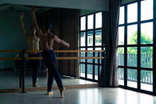 Confidence Caucasian Male Ballet Dancer Practicing Ballet Dance Alone In Studio Room. Handsome Man Athletic Dancing Classic Ballet Showing Performance Body Stretching And Strength Muscle.