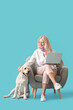 Mature woman with laptop and cute Labrador dog sitting in armchair on blue background