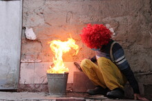 A Male Clown Wearing Red Wig, Sweater, Yellow Pants, Suspenders And Disposable Face Masks Is Sitting Among The Ruins In The Evening Near A Burning Flame In Order To Get Warm. He Looks Scared.