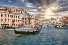 Venetian Gondolier Punting Gondola Through Grand Canal Waters Of Venice Italy Near Rialto Bridge.