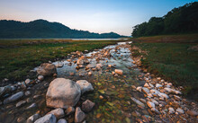Fresh Water Stream Flowing Across Mountain And Forest Valley In Nature Landscape With Rocks And Pebbles At Sunrise