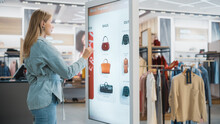 Beautiful Female Customer Using Floor-Standing LCD Touch Display While Shopping In Clothing Store. She Is Choosing Stylish Bags, Picking Different Designs From Collection. People In Fashionable Shop.