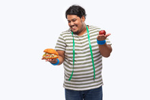 Portrait Of A Fat Man With Measuring Tape Around His Neck Greedily Devouring  A Burger Rather Than Apple.