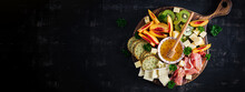 Italian Antipasto Catering Platter With Prosciutto, Cheese And Fruit On A Dark Background. Top View, Banner, Overhead