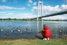Boy Feeding Ducks At The River Bank On Yenisei River On Krasnoyarsk, Russia