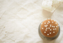 Pin Cushion Of Metal And Antique Orange Fabric, With Ivory Dressmaking Pins.  Arranged On A Linen And Lace Flat Lay