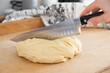 Surowe ciasto na ciasteczka,  nóż krojenia ciasta, na drewnianej desce do krojenia. Wyrobione ciasto na bułeczki. Cukiernia, kuchnia. Nóż szefa kuchni. Damska dłoń trzyma ostry nóż i kroi ciasto.
