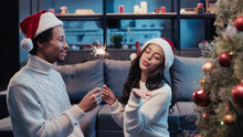 Cheerful African American Man In Santa Hat And Woman Blowing Kiss While Holding Sparkler Near Christmas Tree