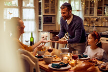 Happy Jewish Father Serves Food To His Family While Celebrating Hanukkah At Dining Table.