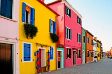 Europe. Italy. Veneto. Burano. The Colorful Houses Of The Village Of Burano And The Leaning Tower.