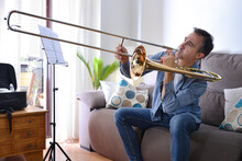 Novice Man Playing Trombone At Home With Enthusiasm
