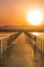 Wooden And Metal Bridge Road Or Pontoon Leading To Bright Picturesque Orange Sunset Over Desert Mountains Of Egypt With Coastline And Reflections In Sea Water At Sunny Vacation Evening. Vertical Image