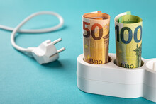 Fifty And One Hundred Euro Banknotes Plugged Into A White Power Strip Over Blue Bacground. Increasing Cost Of Electricity For Customers, Rise In Electricity Prices Concept.