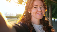Portrait Of Pretty Woman With Long Curly Red Flowing Hair And Freckles Making Selfie Winking Against City Park With Lawn At Sunset Back Light Closeup