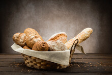 Assortment Of Baked Bread In Straw Basket On Wooden Table