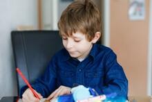 Hard-working School Kid Boy Making Homework During Quarantine Time From Corona Pandemic Disease. Child On Home Schooling In Coronavirus Covid Time, Schools Closed. Homeschooling Concept
