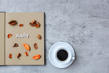 Monday Flat Lay Minimalist Autumn Concept With Book, Dry Leaves And A Cup Of Coffee On Grey Cement Background