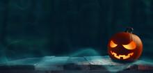 Carved Halloween Pumpkin Jack O Lantern On A Rustic Wooden Plank, Dark Forest, Seasonal Concept