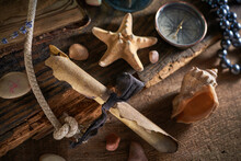 A Marine Concept With A Bottle, Starfish, Seashells, Rope, Compass And Paper Scroll, Pirate Still Life