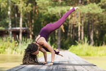 A Woman Practicing Yoga, Performs The Eka Pada Bakasana Exercise, Crane Pose, Stands On A Wooden Bridge In A Park Near A Pond