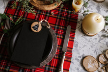 Christmas Table Setting With Empty Menu On Checkered Red Tablecloth