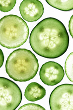 Thin Slices Of Cucumber Shot On A Backlit White Surface