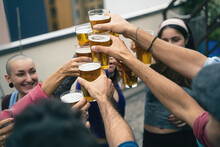 Happy Group Of Young People Toasting With Beer. Multiracial Students Party In The Youth Hostel Terrace.