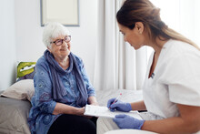 Nurse With Elderly Woman At Home