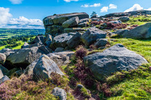Purple Heathers And Rocky Crags On A Summit Of Ilkley Moor Above The Town Of Ilkley Yorkshire, UK In Summertime