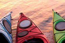 Fragments Of Three Empty Kayaks Over The Water Of The River At Winter Sunrise