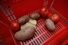 Shallow Depth Of Field (selective Focus) Image With Potatoes, Tomatoes And Bread In A Red Shopping Basket On The Asphalt.