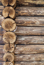 A Wall Of Wooden Logs, Corner Joints Of A Chopped Log House. Vertical Photo