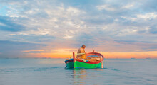 Fisherman With Fishing Boat In A Calm Sea In The Background Amazing Sunset