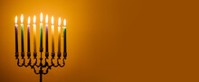 Lights The Menorah For Hanukkah.  Jewish Holiday. Tradition Is A Religious Ritual. Sunset. The First Star. Judaism. Yellow Background Banner. Burning Candle
