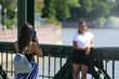 Dziewczyna fotografuje koleżankę telefonem komurkowym, smartfonem na moście.