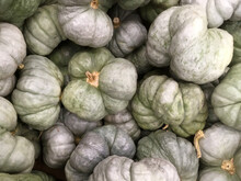 Full Frame Close-up View Of Fresh Pale Green Gray Pumpkins Displayed At A Grocery Market Stand