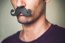 Close Up Of A Man's Chin Wearing A Fake Paper Made Mustache - Movember