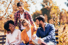 Group Of Young People Having Fun Outdoors On Park Bench
