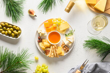 Christmas Party With Cheese Platter, White Wine, Olive, Different Cheese, Fruits On A White Background. Top View. Appetizer For Party.