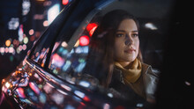 Stylish Female Is Commuting Home In A Backseat Of A Taxi At Night. Beautiful Woman Passenger Looking Out Of Window While In A Car In Urban City Street With Working Neon Signs.
