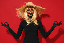 Young Woman With Halloween Makeup Mask Wears Straw Hat Black Scarecrow Costume Hold Hands Yoga Om Aum Gesture Relax Meditate Isolated On Plain Red Background Studio Celebration Holiday Party Concept.