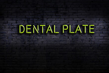 Neon Sign. Word Dental Plate Against Brick Wall. Night View