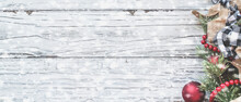 Top View Of Christmas Ornaments And Trimmings Against A White Rustic Table With Snow Flakes. Top View Web Banner.